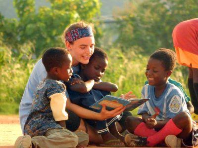 """Im Projekt """"Lesen auf dem Fußballplatz"""" in Ghana liest eine Freiwillige den Kindern aus einem Buch vor"""