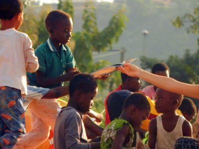 Ein Kind bekommt ein Buch von einem Freiwilligen im Fußball- und Leseprojekt in Ghana