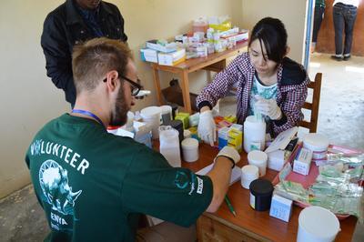 Ein Freiwilliger im Medizin - Projekt in Kenia arbeitet mit einer Krankenschwester an Medikation für Patenten