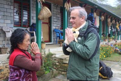 Peter Slowe grüßt eine Dorfbewohnerin in Nepal