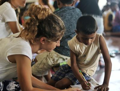 Freiwillige bei Schreibübungen mit einem Schüler in Sri Lanka
