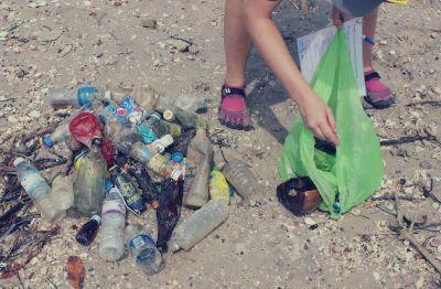 Frivillig indsamler skrald på stranden
