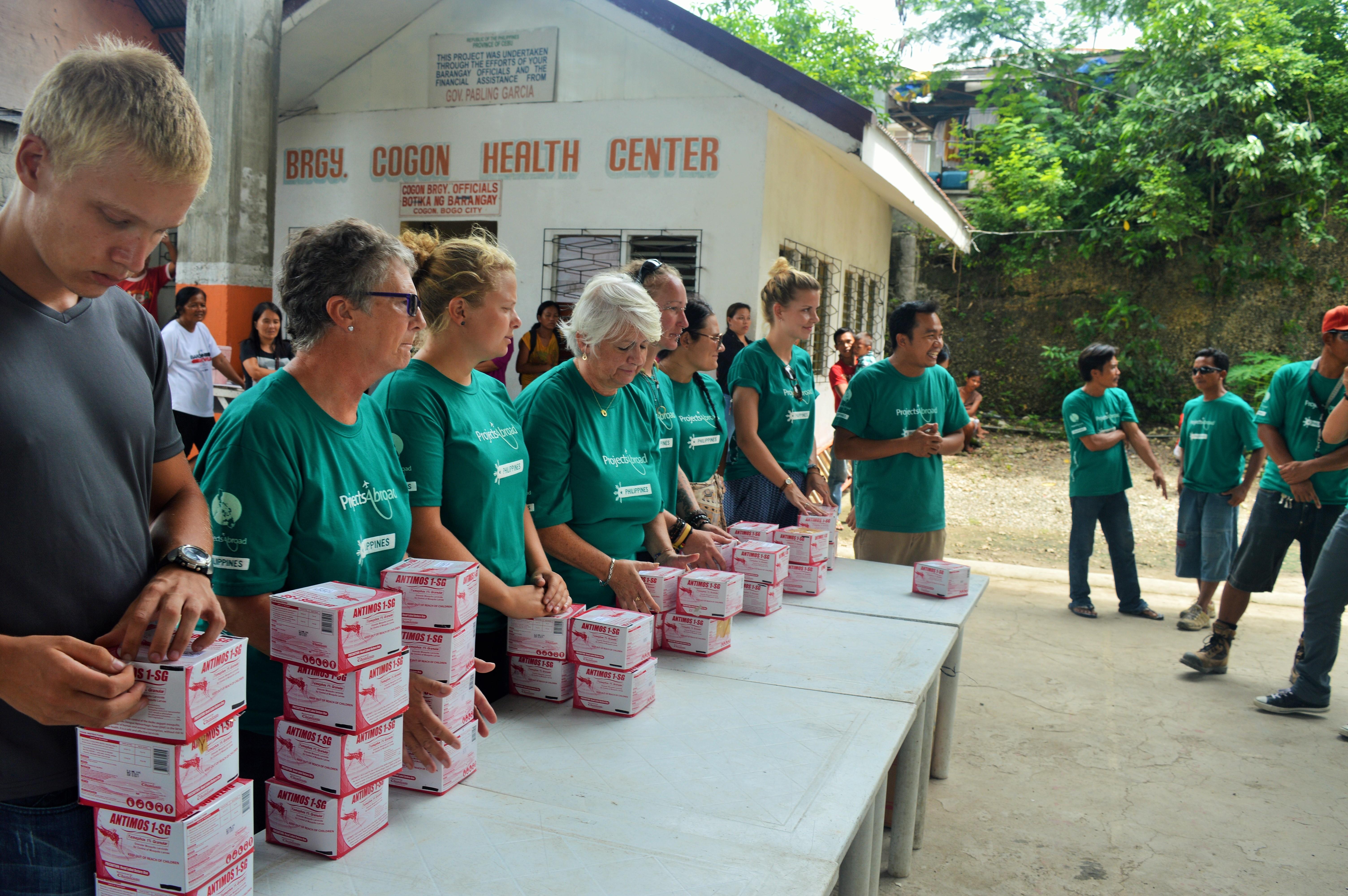 Projects Abroads frivillige uddeler kasser med larvicider til de locale under en kampagne for at forebygge spredning af Dengue-feber I Filippinerne.