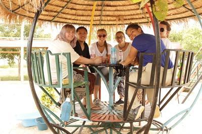 Projects Abroad frivillig, Alice Bowman fra Scotland, sidder med en gruppe frivillige og lokalt personale på et humanitært projekt i Cambodja