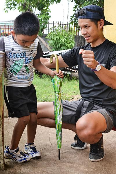 Frivillig fra Projects Abroad projekt inden for fysioterapi, Victor Lee, sammen med ung dreng som er en af hans ambulant patienter.