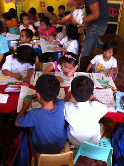 Filippinske børn sidder og tegner i deres malebøger