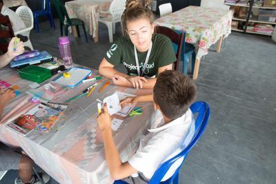 En frivillig sidder sammen med en dreng på læseprogrammet i Belize