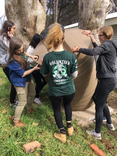 Frivillige hjælper med at installere en regnvandstønde
