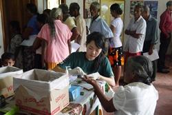 Projects Abroad Medicine volunteer from Hong Kong tests blood sugar and blood pressure at medical outreach camp in rural Colombo