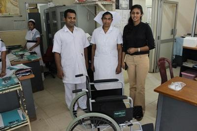 Projects Abroad staff member and local staff from the National Cancer Institute stand by a wheelchair that was donated to the male medical ward.