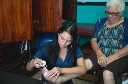 Un anciano recibe tratamiento con electrodos de un voluntario de Projects Abroad por un problema en el pie en la Asociacion Centro de Atención al Anciano Francisca Valerio Badilla