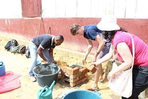 Voluntarios de Trabajo Social de Projects Abroad junto a miembros del personal local construyen un horno para hervir agua para tener agua potable en la escuela local en Andasibe, Madagascar
