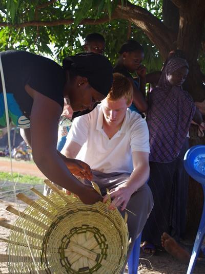 Mujer togolesa enseña a un voluntario del proyecto de Desarrollo Internacional cómo tejer una canasta