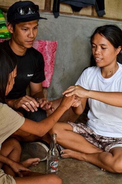 Un voluntario del proyecto de Fisioterapia de Projects Abroad le enseña a una madre joven y su hija cómo realizar los ejercicios