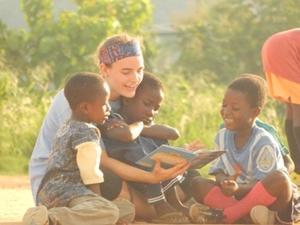 Niños y una voluntaria leen un libro en Ghana