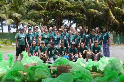 Un groupe de volontaire se trouve derrière un tas d'ordures, collectées durant le nettoyage des plages de Panadura