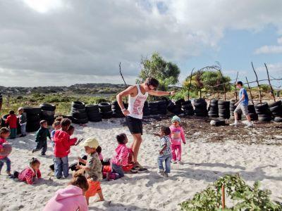 Volontaire avec les enfants de la crèche annexe au site du chantier construction au Cap