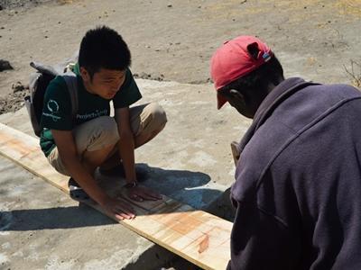 Un volontaire et un local coupent du bois ensemble à Esere en Tanzanie