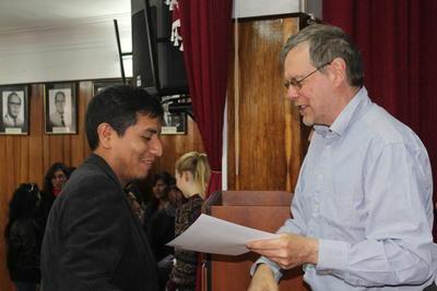 Un volontaire en enseignement remet son certificat à un professeur ayant participé au programme de formation