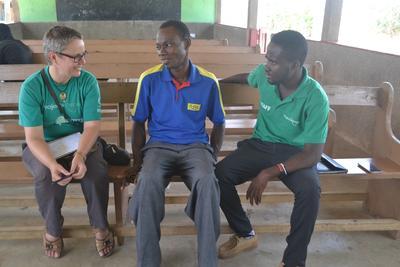 Une volontaire parle avec un bénéficiaire du projet de microfinance au Ghana