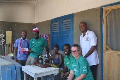 Les volontaires en microfinance posent avec Victoria qui tient une boutique d'artisanat au Ghana