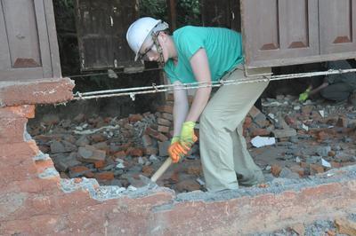 Un volontaire en reconstruction frappe sur un mur avec une masse pour le détruire