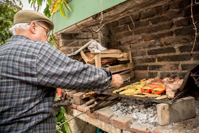 Un homme prépare un barbecue argentin pour les fêtes de Noël