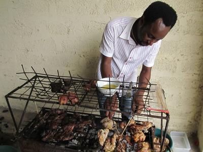 En Tanzanie, un homme prépare un barbecue pour griller de la viande