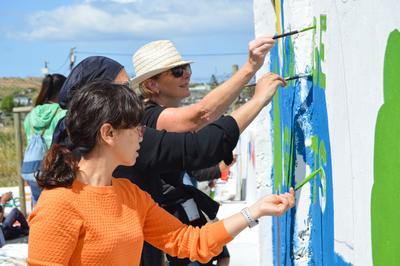 Des volontaires peignent une fresque éducative sur un projet sans conditions de compétences