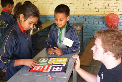 Projects Abroad teaching volunteer plays games with young children at Deepmala's English camp during school holidays, in Nepal.