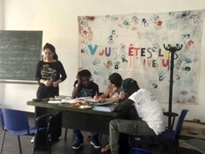 Una volontaria insegna italiano ad una classe di rifugiati in Italia