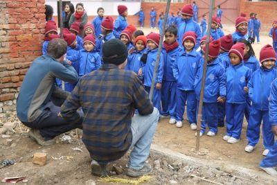 Un volontario con i bambini di una scuola appena ricostruita dopo il terremoto in Nepal