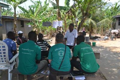 Volontari e staff locale del progetto di microcredito in Ghana insieme a Victoria, proprietaria di un negozio di artigianato