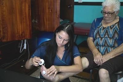 プロジェクトアブロードの理学療法ボランティアがコスタリカでお年寄りに電気治療を行っています。