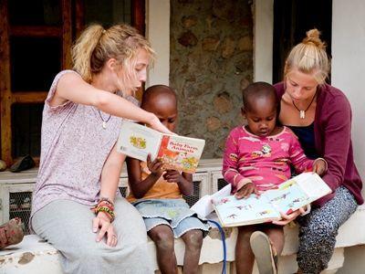 プロジェクトアブロードタンザニアの教育プロジェクトのボランティアが担当場所で小さな子供に読み聞かせをしているところ