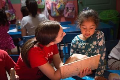 プロジェクトアブロード教育ボランティアがコスタリカの地元の学校で、小さな女の子に読み聞かせしているところ