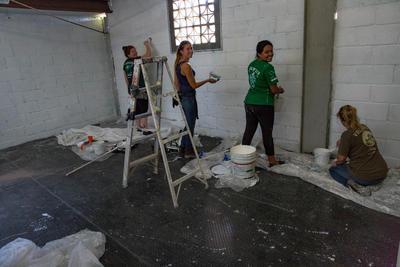 ボランティアとスタッフが、オープニングセレモニーに向けて移民宿泊施設のペインティングを行っている場面