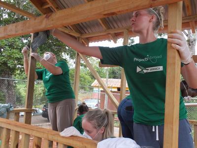 ジャマイカの建築ボランティアたちが、遊び場におままごと用の家を建設している様子
