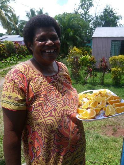 Een lokale vrouw in Fiji met appelsienen