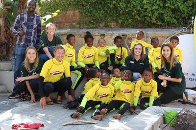 Projects Abroad Nutrition volunteers sit with children from the Surfing project in Cape Town, South Africa