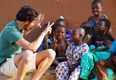 In Togo praat een vrijwilliger van het Internationale ontwikkelingsproject met lokale kinderen