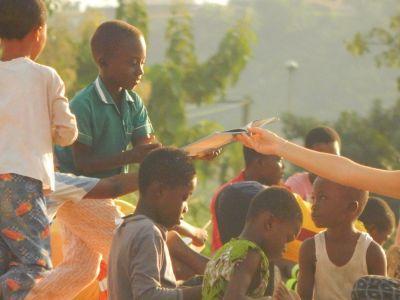 Op een voetbalveld in Ghana krijgt een jongen een boek aangereikt.