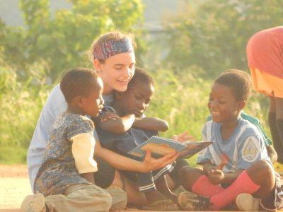 Kinderen in Ghana worden voorgelezen door een vrijwilliger op het voetbalveld