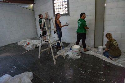 Vrijwilligers en medewerkers verven de muur van de nieuwe slaapzaal ter voorbereiding van de inwijding in het FM4 Paso Libre migraten opvangcentrum.