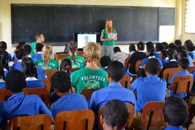 Een vrijwilligster praat tegen een aantal jonge Fijiërs tijdens een haai onderwijs initiatief