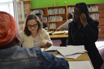 Maria helpt een vrijwilliger van het Mensenrechten project tijdens een juridisch loket in een township in Kaapstad.