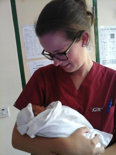 Student Rachel houdt een pasgeboren baby vast tijdens haar verpleegkunde stage in Ghana.