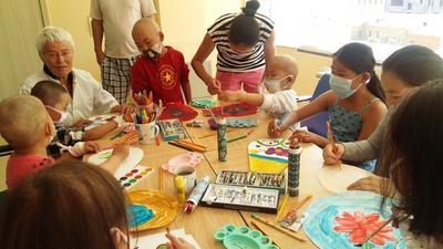 Vrijwilliger geeft creatieve therapie aan kinderen met kanker op het sociale zorg project in Mongolië