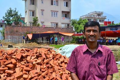 Surendra Maharian, rektor på Sunriseskolan, står vid byggplatsen där volontärer hjälper till att bygga   den nya skolan i Kathmandu, Nepal.