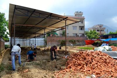 Innan de kan gjuta cement och lägga tegel, gräver volontärer ut grunden för den nya Sunriseskolan i Kathmandu, Nepal